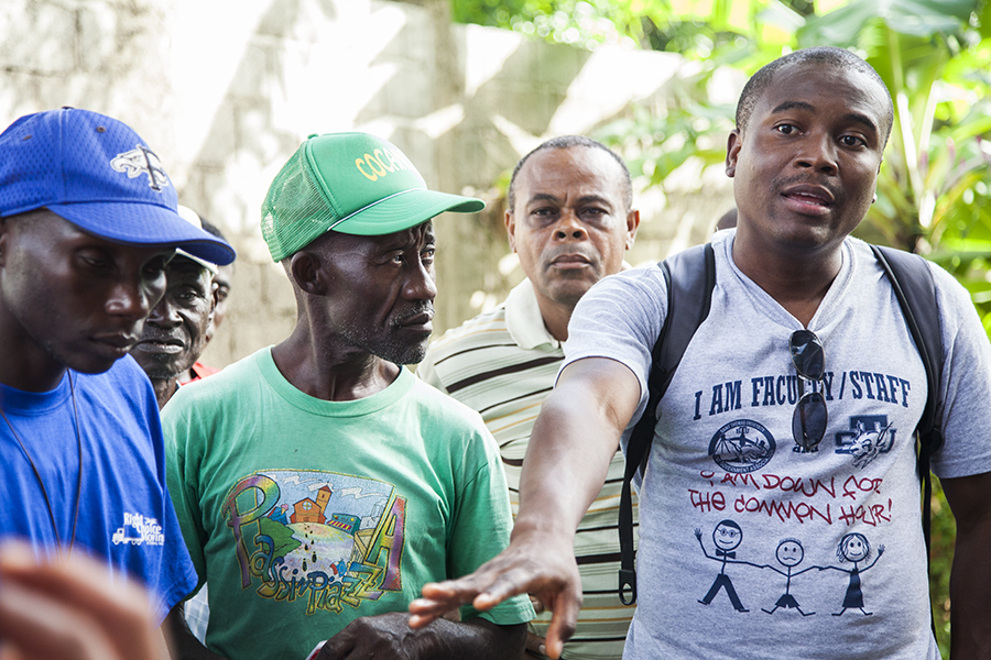 Emmanuel Buteau, St. Thomas doctoral student, speaks with COCANO coffee farmers (from left) Petit Frere Lafontant, Eliocoer Beaubrun, and Ferdinand Louis in San Louis du Nord, Haiti.